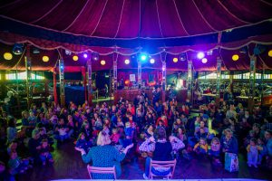Children sat around in a circus tent